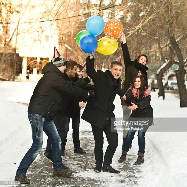 Group of young friends with party hats and balloons