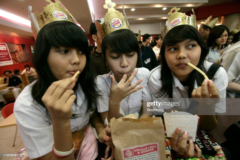 A group of young girls eat their Burger King meals on the opening day of the first Burger King Holdings Inc. fast food restaurant in Indonesia, at the Senayan City shopping mall in Jakarta, on Thursday, April 26, 2007. Burger King Holdings Inc., the world's second-largest burger chain, will open fast food restaurants in Japan and Hong Kong next. Photographer: Dimas Ardian/Bloomberg via Getty Images News