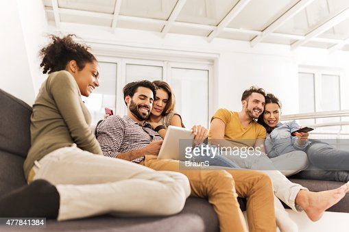 Group of young happy friends relaxing together at home.