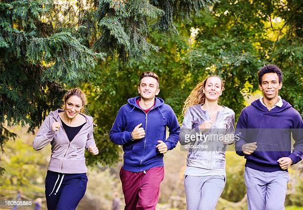Group of Young Happy Friends running in park