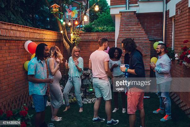 Groupe de jeune heureux de gens danser au parti jardin.
