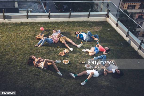 Group of young happy people lying on grass and enjoying a day on a terrace.