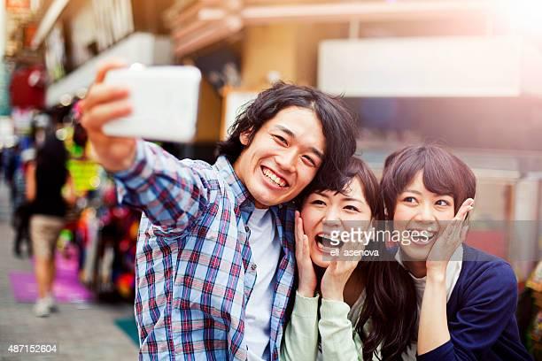 グループの若い青年を飾る人々の自分撮り、東京、