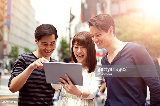 Group of young japanese people with digital tablet, Shibuya, Tokyo.
