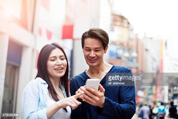 グループの若い日本人に、スマートフォン、渋谷、東京。