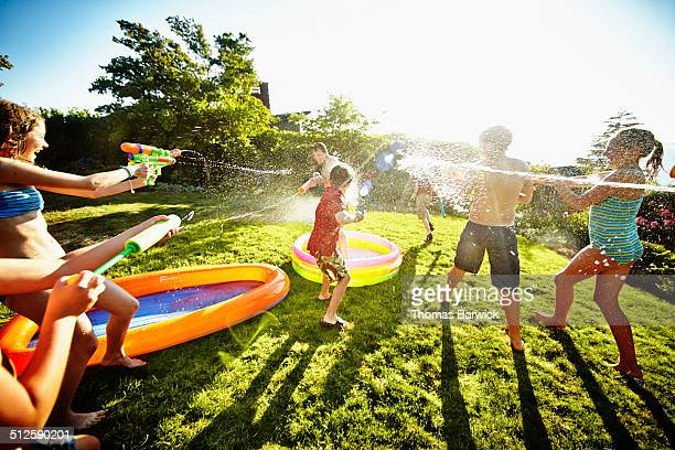 Group of young kids having water fight against dad