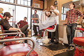 Group of young male adult friends chatting in barbershop