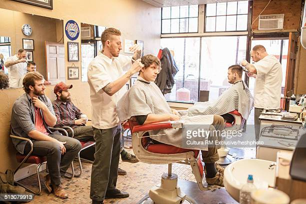 Group of young male adults waiting and having haircut in barbershop
