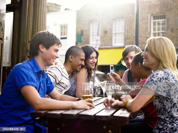 Group of young men and women at pub table, outdoors