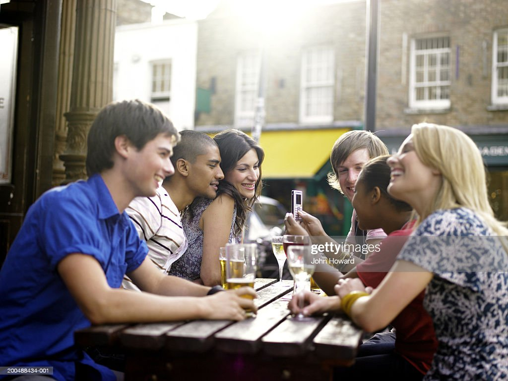 Group of young men and women at pub table, outdoors : Stock Photo