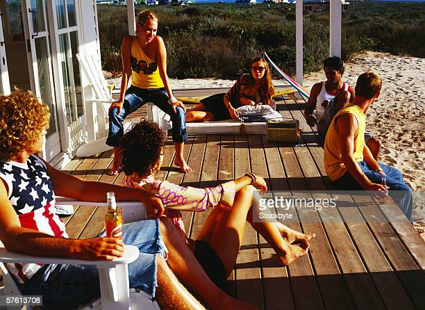 Group of young men and women drinking beer on the porch of a beach house
