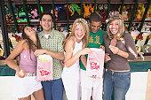 Group of young men and women eating popcorn, amusement park, portrait