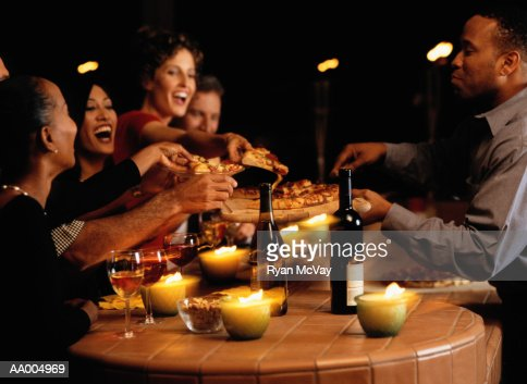Group of young men and women in bar, sharing pizza : Stock Photo