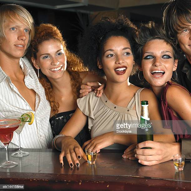 group of young men and women standing together at the bar