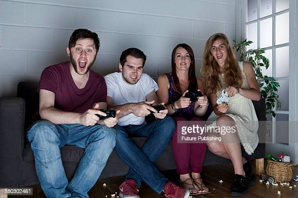 A group of young men and women with cheerful expressions playing Sony PlayStation 3 video games on a sofa taken on July 9 2013