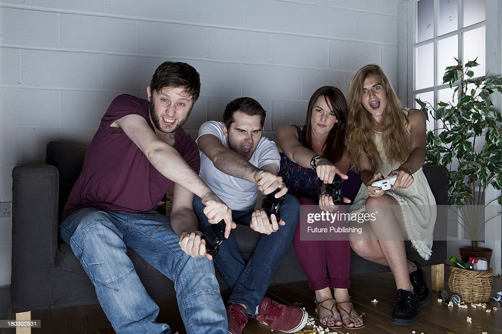 A group of young men and women with strained expressions playing Sony PlayStation 3 video games on a sofa, taken on July 9, 2013.