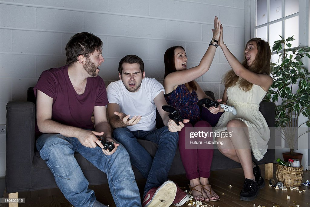 A group of young men and women with various expressions of happiness, anger and confusion playing Sony PlayStation 3 video games on a sofa, taken on July 9, 2013.