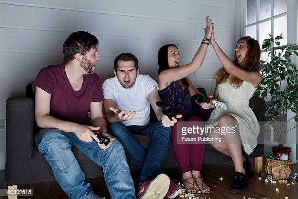 A group of young men and women with various expressions of happiness anger and confusion playing Sony PlayStation 3 video games on a sofa taken on...