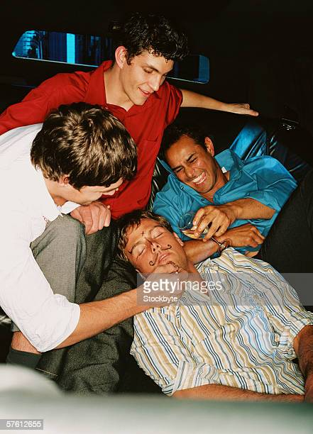 Group of young men drawing on a sleeping man's face