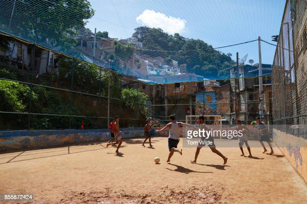 Group of young men playing football on a dirt court in Rio