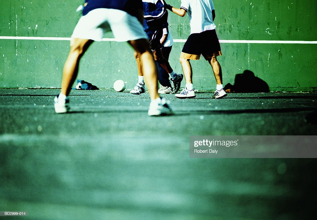 Group of young men playing football on sports court (cross-processed) : Stock Photo