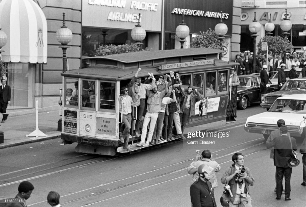 A group of young men raise their fists as they ride a street car on Powell Street as they pass the St Francis Hotel where President Nixon was due to...