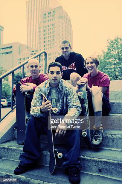 Group of young men sitting on steps with skateboards, portrait