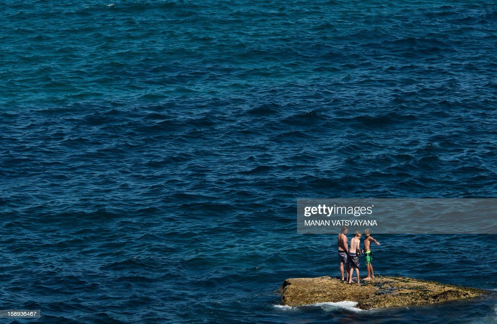 A group of young men stands atop a rock in the waters around the popular Bondi beach in Sydney on January 4, 2013. Australia's southern island of Tasmania has experienced its hottest day since records began, with the capital Hobart sweltering at 41.8 Celsius (107.2 Fahrenheit) on January 4. In Australia's biggest city Sydney, thousands headed to beaches to escape the heat but the temperature was much milder, hitting a maximum of just 29 Celsius (84 F) in the city centre.