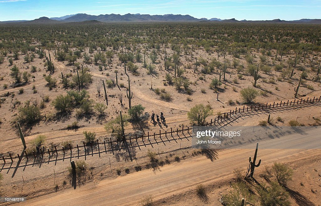 A group of young men walk along the Mexican side of the USMexico border fence in a remote area of the Sonoran Desert on December 9 2010 in the Tohono...