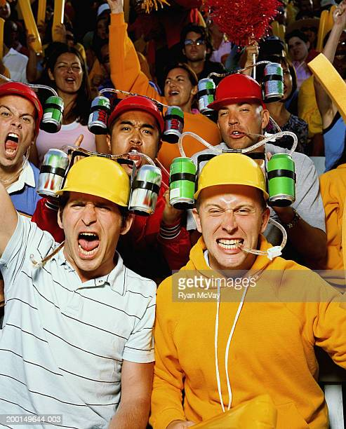 Group of young men wearing drinking helmets, cheering in crowd