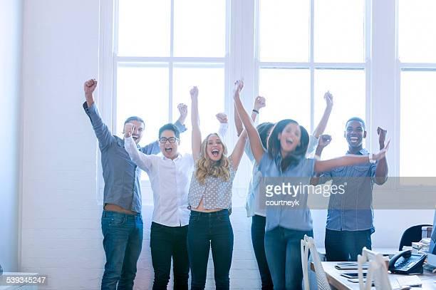 multi-kulturelle Gruppe junger Geschäftsleute feiert.