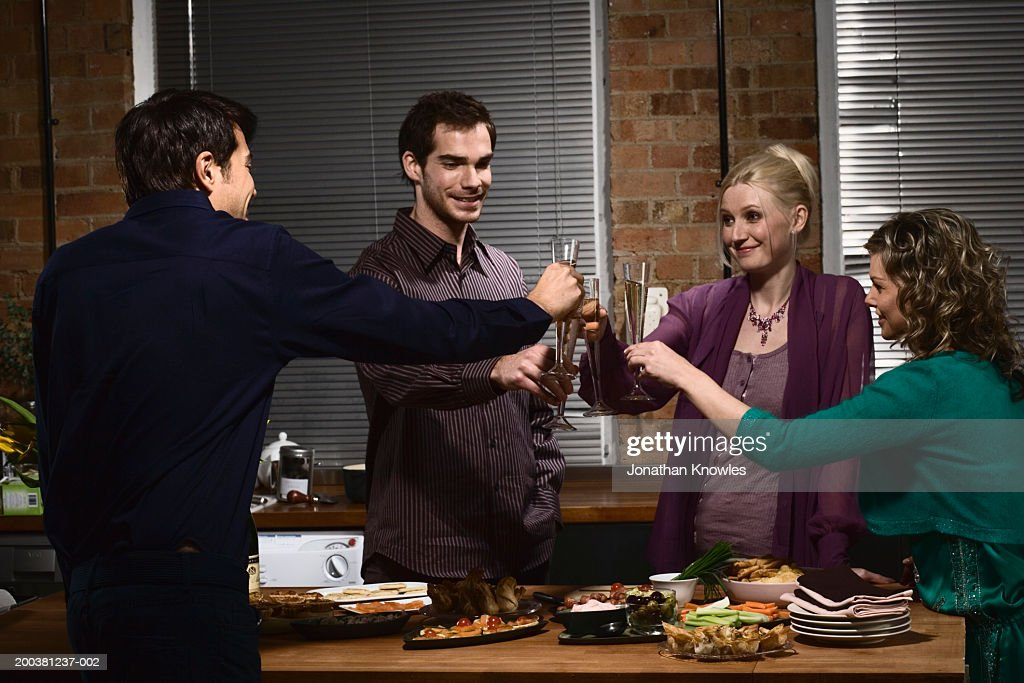 Group of young people at party, raising glasses of champagne for toast : Stock Photo