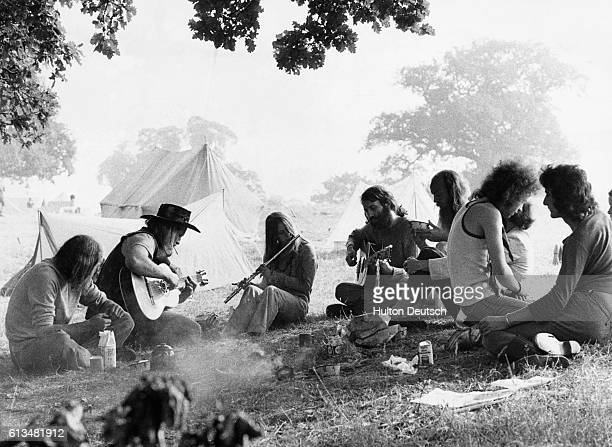 A group of young people attending the 1973 pop festival at Windsor Great Park hold an impromptu playing session of their own during a meal