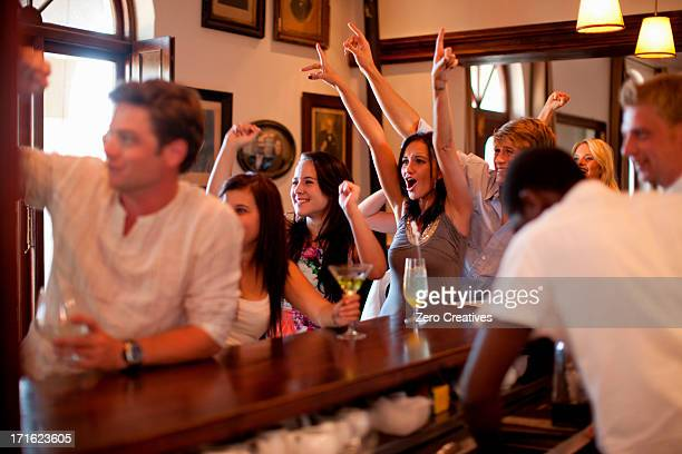 Group of young people cheering in bar