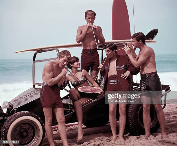 A group of young people cluster around their sand buggy to drink juice straight from a watermelon 1966