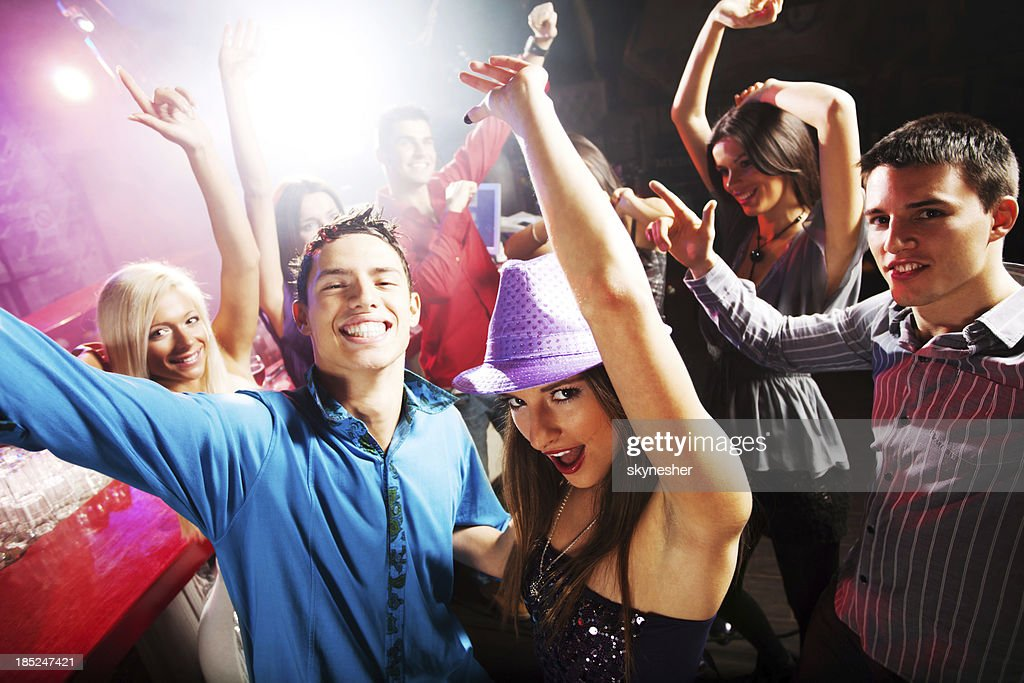 Group of young people dancing at the discotheque.