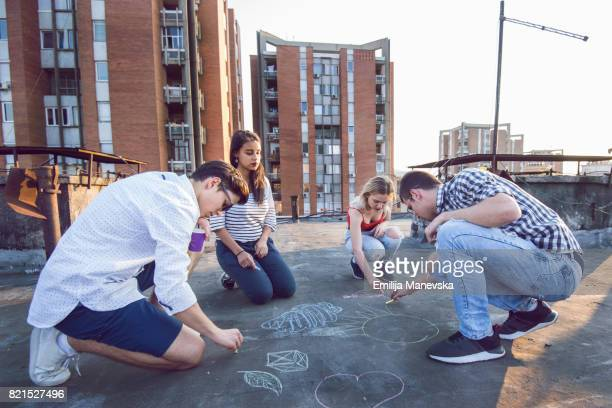 Group of young people drawing with chalk at the roof top