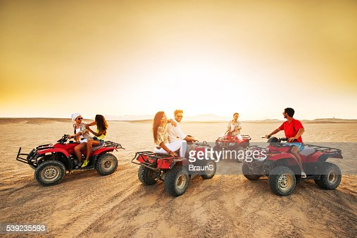 Group of young people driving quad bikes at sunset.