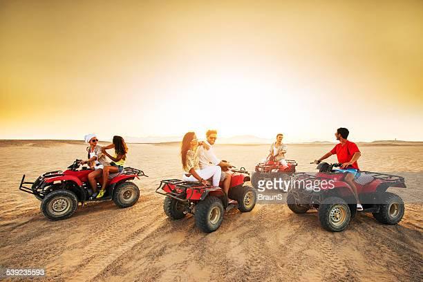 Grupo de jovens de condução quad bicicletas ao pôr do sol.