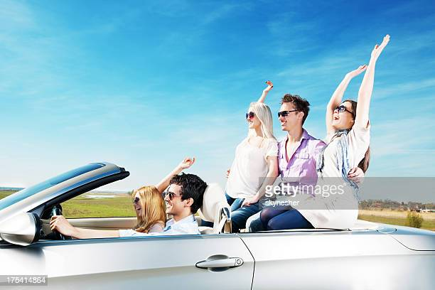Group of young people enjoying in a Convertible car ride.