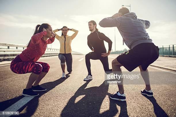 """Groupe de jeunes gens faire de l """" exercice sur un route."""