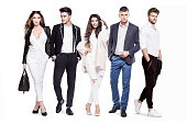 Group of young people fashionably and elegantly dressed standing on a white background