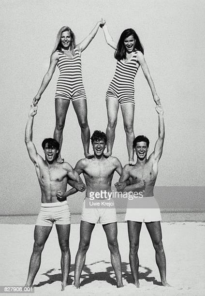 Group of young people forming human pyramid, portrait (B&W)