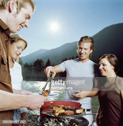 Group of young people gathered around barbecue at riverside : Stock Photo