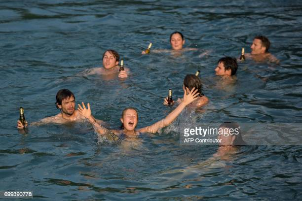 A group of young people have a swim with a beer in the hand while swimming into the river Aare on June 21 2017 in Bern Europe sizzled in a...