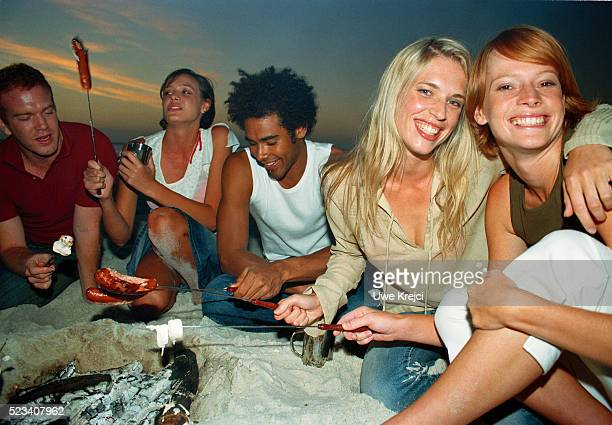 Group of young people having a barbecue on the beach