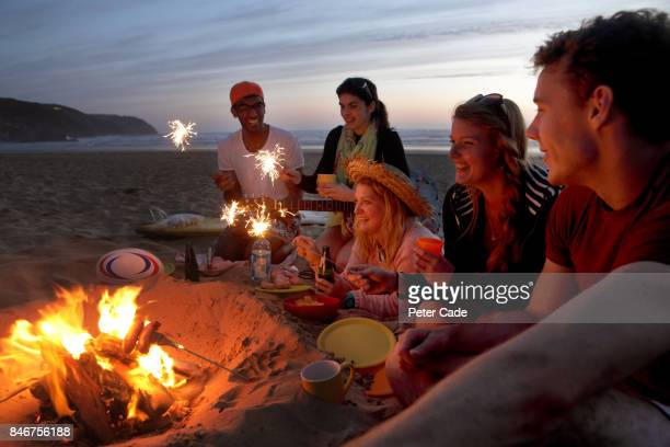 Group of young people having fire on beach in the evening