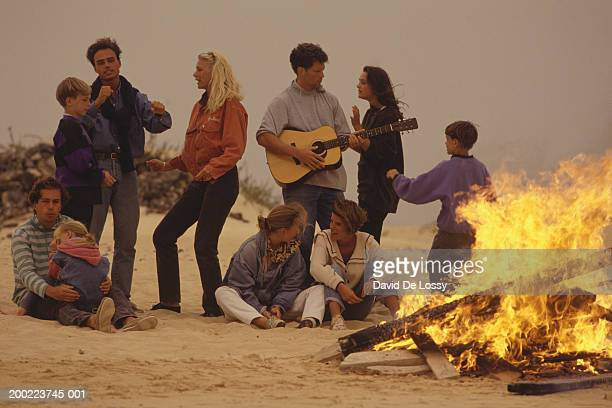 Group of young people having fire on beach