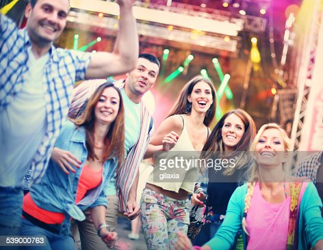 Group of young people having fun at concert.