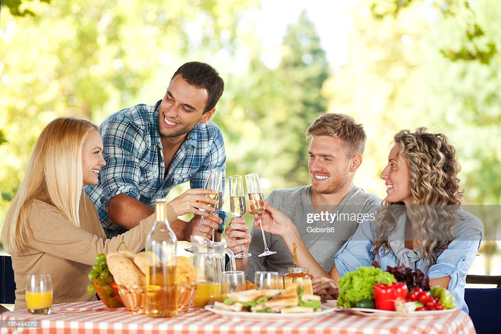 Group of young people having picnic in park : Stock Photo